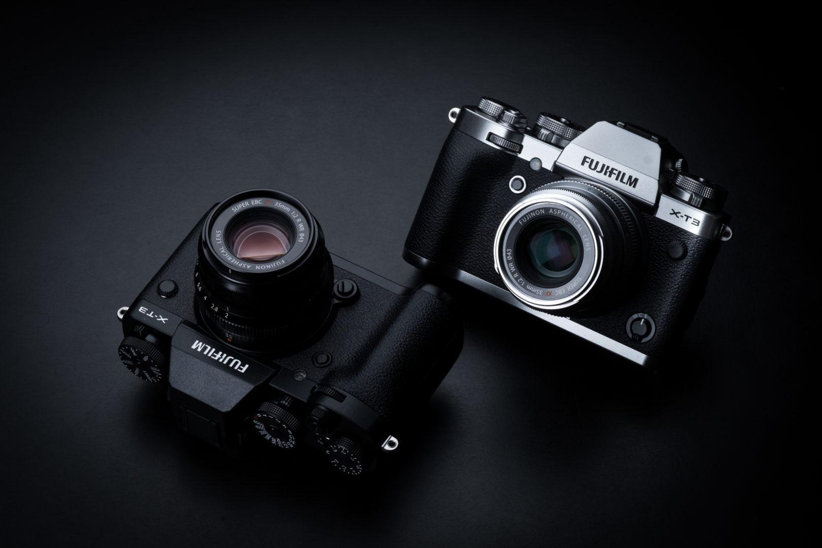 Duas câmeras Fujifilm mirrorless X Series em um fundo escuro. O modelo é X-T3, uma de cor preta e outra prateada.