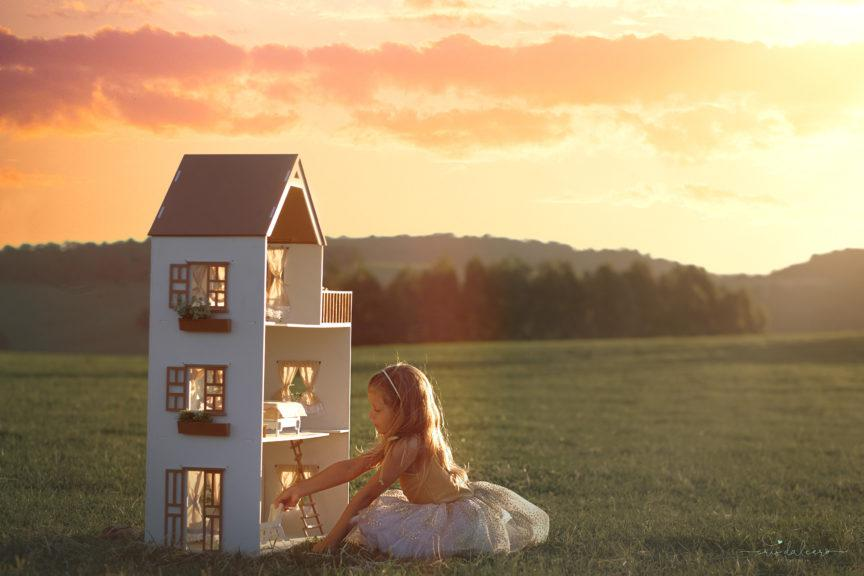 Menina brincando de casinha em um cenário mágico. Campo verde e nuances alaranjadas do sol deixam o ambiente com aparência bucólica.