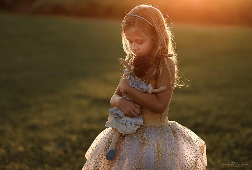 Menina brincando com uma boneca na mão, sendo iluminada pela luz do sol no campo.