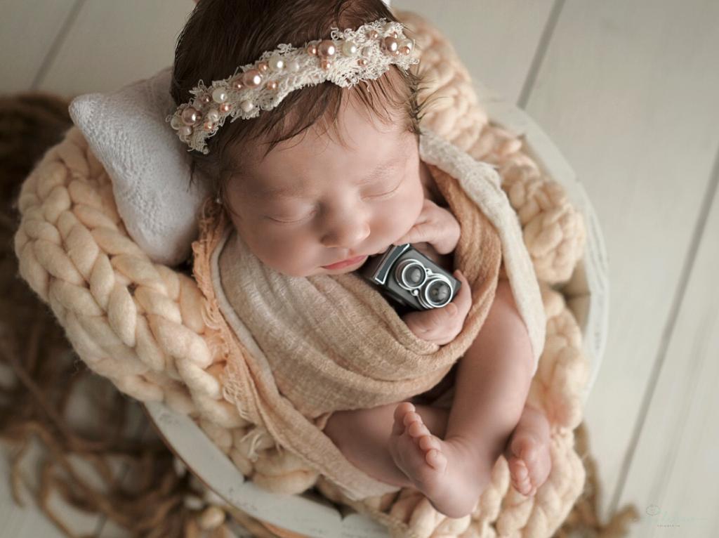 Foto de bebê recém nascido com uma tiara de flores e uma miniatura de câmera nas mãos
