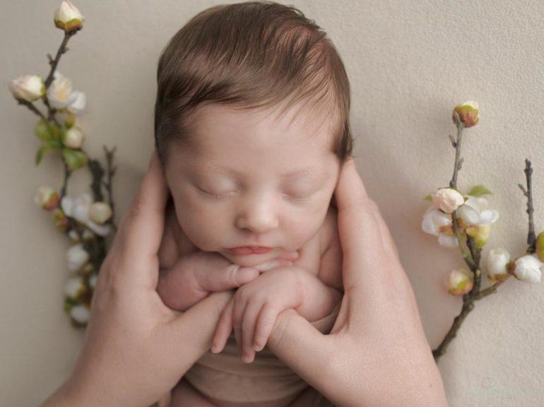 Foto de bebê recém nascido nas mãos da mãe sobre uma superfície com flores