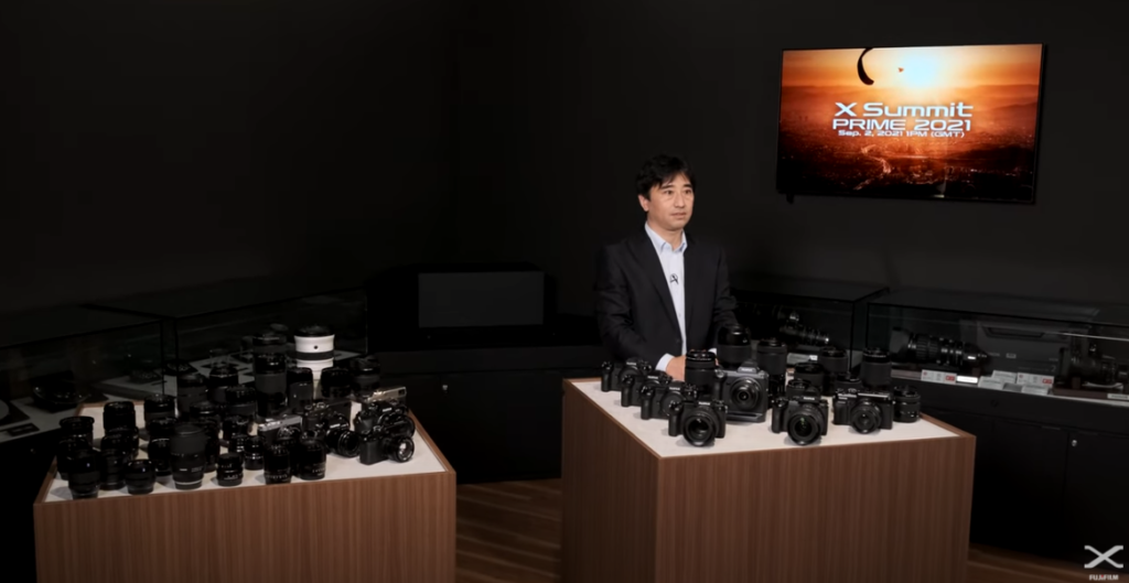 apresentador atrás de balcão com várias lentes e câmeras X Series e uma televisão com o logo do evento